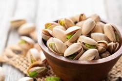 Close up of pistachios in a bowl set against an old wooden backdrop