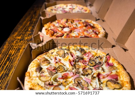 Close up of pizzas with variety of toppings and cheese in cardboard take out boxes with open lid on wooden table #571691737