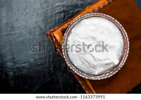 Close up of plain curd or yogurt or dahi in transparent glass bowl on a brown cloth or napkin on wooden surface.