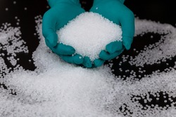 Close-up of plastic polymer granules. hand hold Polymer pellets. polymer plastic. compound polymer. Hands in rubber gloves hold plastic pellets.