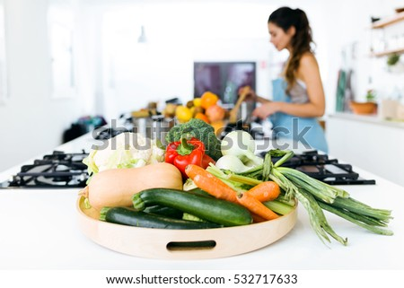 Close-up of plate of fresh vegetables and beautiful young woman cooking in the background.