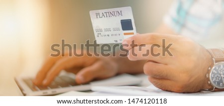close up of platinum credit card in hand with background of blured laptop keyboard #1474120118