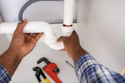 Close-up Of Plumber Fitting Sink Pipe In Kitchen At Home