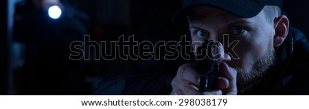 Close up of policeman aiming to the bandit