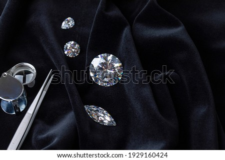 Close up of polished diamonds different cuts and sizes with tweezers and magnifying glass on black velvet fabric top view with copy space.