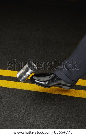 close up of politicians shoe kicking a dented shiny can down the road, space for copy