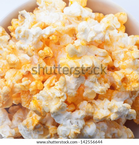 Close up of pop corns in the bowl on white background