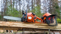Close-up of portable chain saw and safety helmet on wood in metal sawhorse. Professional orange power chainsaw and protective hard hat with face shield of grid mesh on wooden log. Sawing machine tool.