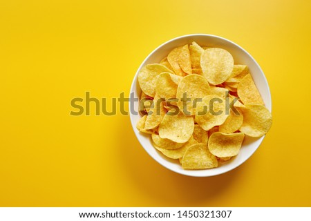 Close-up of potato chips or crisps in bowl against yellow background