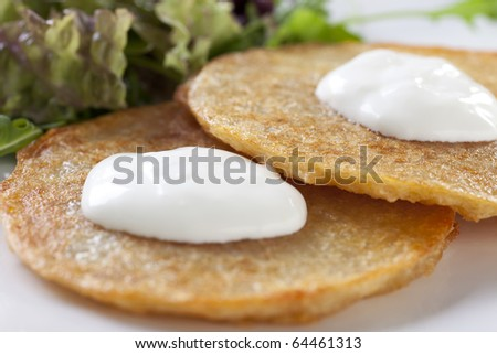 Close up of potato pancakes with sour cream
