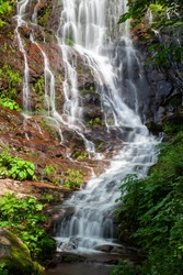 Close-up of powerful Pilj waterfall on Old mountain (Stara planina) in Serbia, cascading down the wet, red rocks and surrounded by vivid green trees