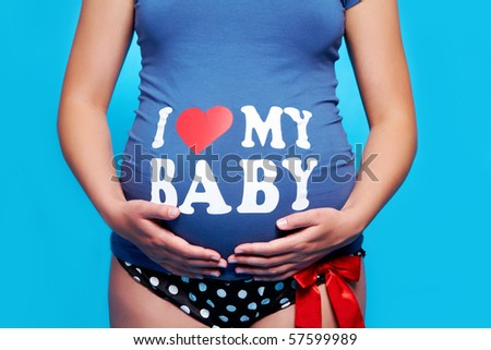 Close-up of pregnant woman touching her stomach over blue background