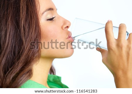 Close-up of pretty girl drinking water from glass