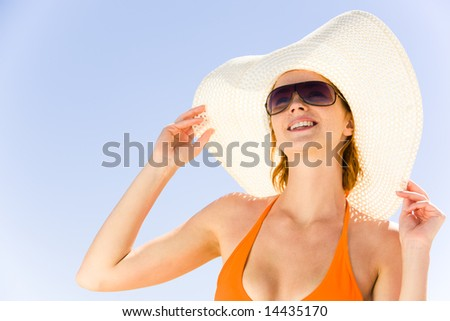 Close-up of pretty girl in hat and sunglasses on the background of blue sky