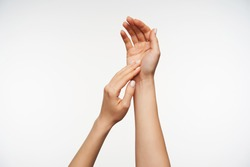 Close-up of pretty lady's hands touching gentle each others while posing over white background, keeping hands raised while lathering hands