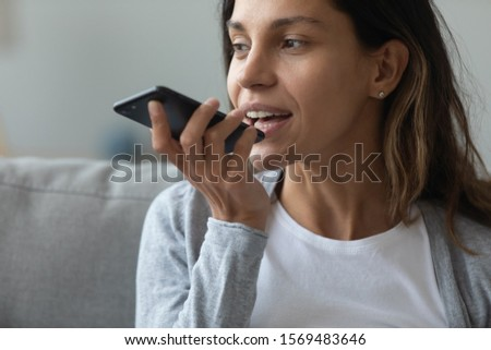 Close up of pretty woman holding in hand smart phone talking with digital assistant or friend distantly uses easy voice messaging, concept of modern ai technology, voice recognition, online translator