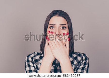 Close up of pretty young surprised woman covering mouth with her hands standing against gray background #583430287
