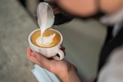 Close up of Professional Barista or waiter pour stream milk to make latte art on specialty coffee. Business cafe owner create image of a leaf on a cup of Espresso for customer. Food, Drink and Routine