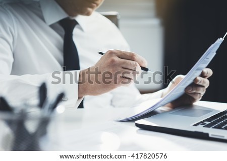 Close-up of professional businessman working at his office with documents, young lawyer using laptop computer and signing contract at comfortable interior, flare light