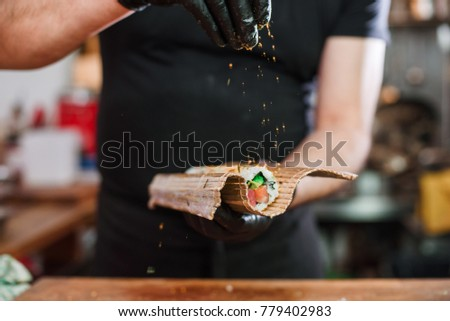 Close-up of professional chef's hands in black gloves making sushi and rolls in a restaurant kitchen. Japanese traditional food. Preparation process.