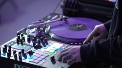 Close-up of professional DJ working behind mixer. Art. Cool DJ quickly switches buttons on mixer. Professional and fast DJ behind mixer