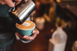 Close-up of professionally extracting coffee by barista with a pouring steamed milk into coffee cup making beautiful latte art. coffee, extraction, deep, cup, art, barista concept.