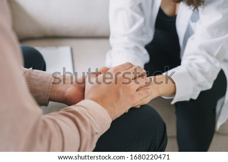 Close-up of psychiatrist hands together holding palm of her patient.  Psychological male comforting and holding a woman hand while sitting on the sofa. psychologist concept Foto stock ©