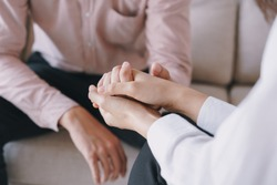 Close-up of psychiatrist hands together holding palm of her patient.  Psychological women comforting and holding a male hand while sitting on the sofa. psychologist concept