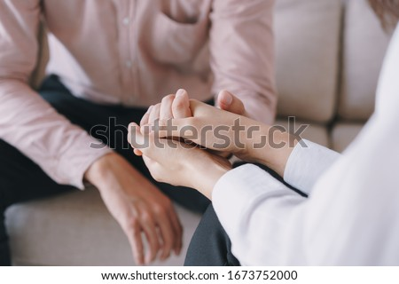 Close-up of psychiatrist hands together holding palm of her patient.  Psychological women comforting and holding a male hand while sitting on the sofa. psychologist concept Foto stock ©