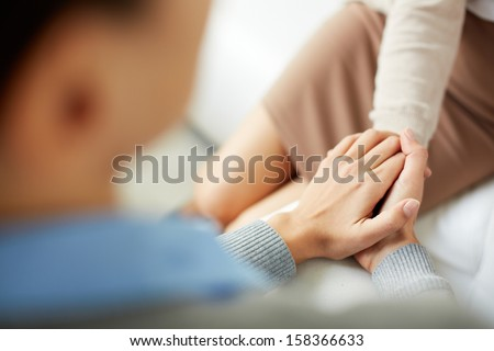 Close-up of psychiatrist keeping her hands together while listening to her patient