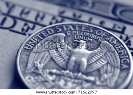 close-up of quarter dollar coin on the one hundred Dollar bill