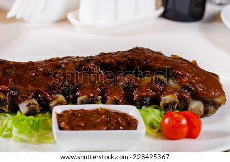 Close Up of Rack of Saucy Barbecue Pork Ribs with Dipping Sauce Served on Plate in Restaurant