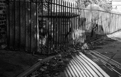 Close up of railings and their shadows beside a pathway at St Nicholas Church, Chiswick, London UK, photographed with high contrast in late afternoon on a sunny day in February.