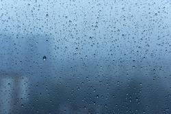 Close-up of rain drops on a window pane. Gloomy damp weather.