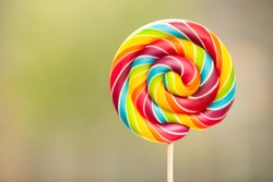 Close up of rainbow colored lollipop. On left is empty space to put text or something else. This file is cleaned and retouched.