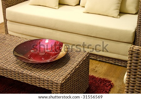 Close up of rattan table with red decoration dish.