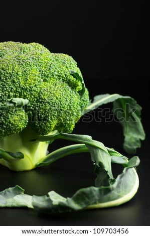 Close-up of raw broccoli on black background.
