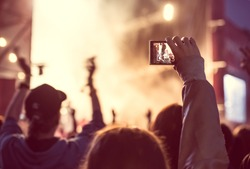 Close up of recording video with smartphone during a concert. Toned picture