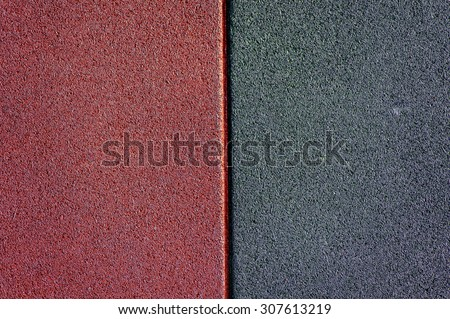 Close up of red and black used and old rubber floor of children play ground