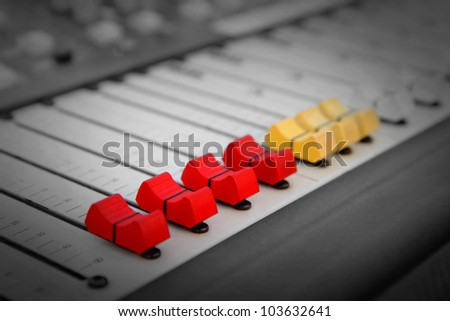 Close up of red and yellow audio sound mixer with buttons