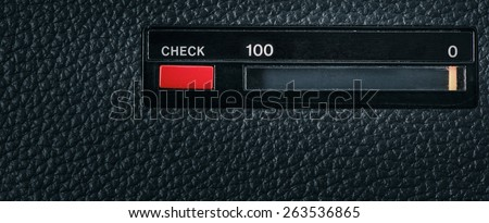 Close up of red check button on old retro technology equipment and scale with the numbers 0 and 100. Can be used as a conceptual image of classic old technology, testing or market research.