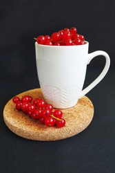 close-up of red currant berries in a white mug on a brown stand on a dark background side view . summer seasonal red berries