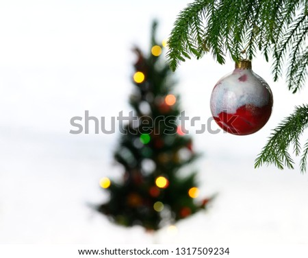 Close up of red glass ball hanging on a pine tree with a distant blurry Christmas tree with lights surrounded by snow
