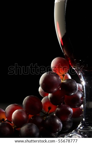 Close-up of red grapes and a glass of red wine