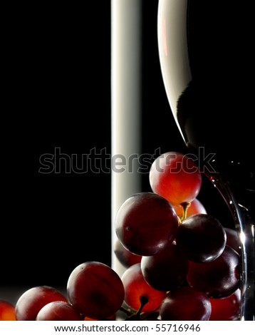 Close-up of red grapes with glass and bottle in background