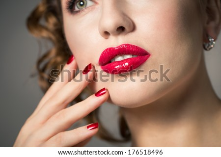 Close-up of red lips and polished nails