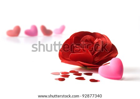 Close up of red paper rose, pink heart and heart confetti. Isolated on white with blurred roses in the background. Copy space.
