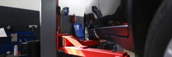 Close-up of red pillaring stand used for automobiles and sportcars examinations and lifting heavy machinery. Hardworking people mechanics repair differential and engines indoors