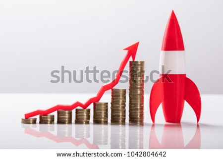 Close-up Of Red Rocket Besides Stacked Coins And Arrow Showing Upward Direction