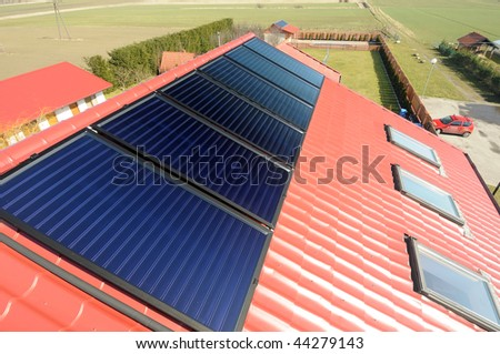 Close up of red roof with solar panels. Green field  in background.